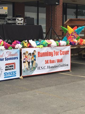 "Banner reading ""Running for Cover 5K Run / Walk, HSC Homeless Coalition"" hanging on the front of the stage."