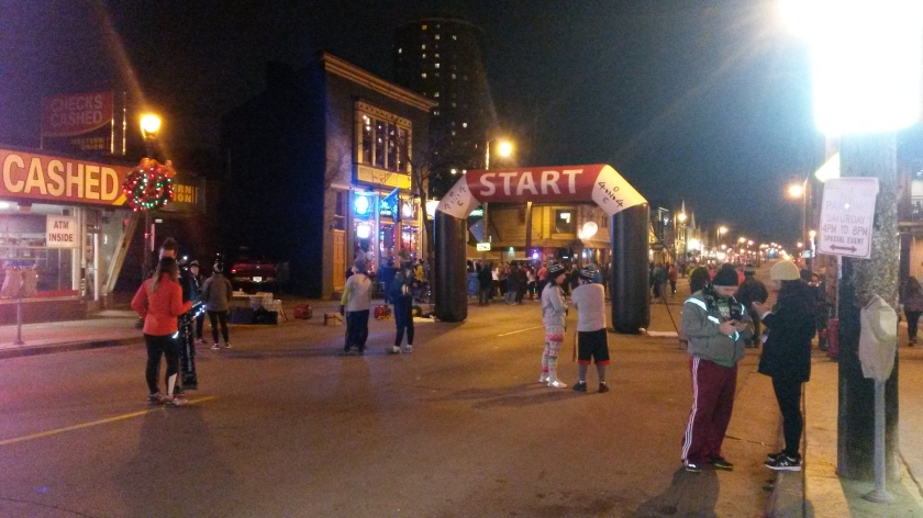 "Nighttime; a sparse crowd of runners by an inflatable ""Start"" arch in the middle of a city street with assorted Christmas decorations."