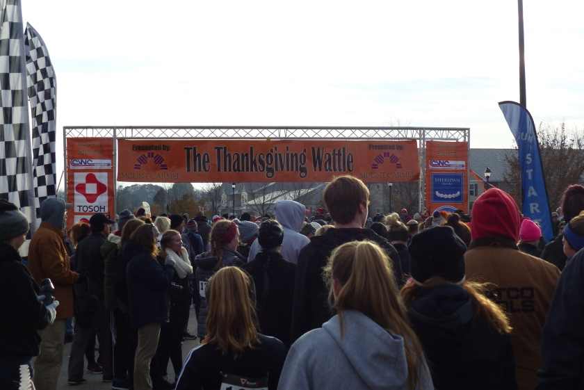 "Runners mingling in front of an orange banner reading ""The Thanksgiving Wattle"""