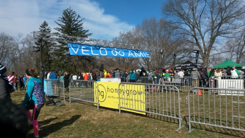 "Runners milling around outside the barricades of the race starting area. A blue banner reading ""Velo Amis"" is stretched out above the starting line."